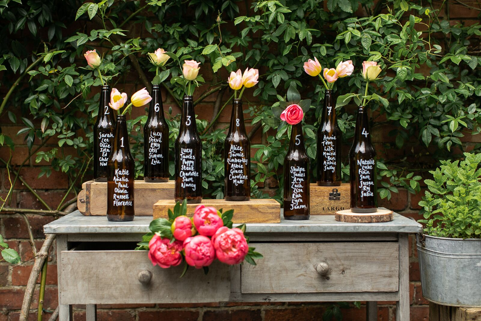 Glass bottle table plan on rustic table at a traditional courtyard wedding