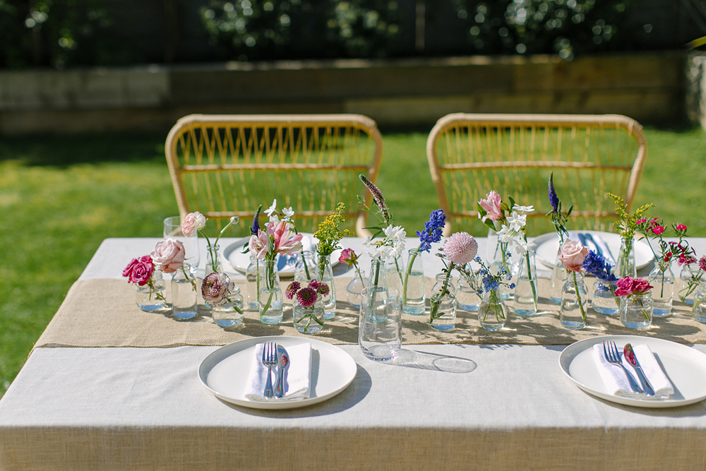 Floral wedding centrepiece with mini glass vases and bottles and single stems of brightly coloured spring flowers on a linen tablecloth