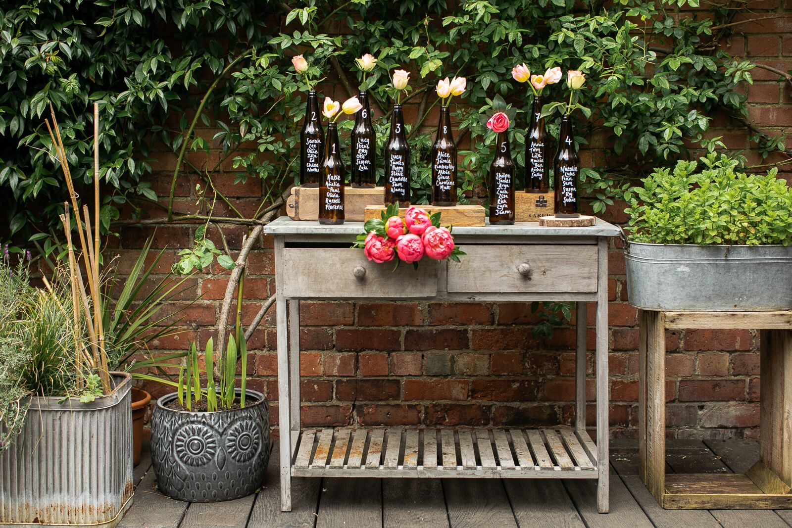 Glass bottle table plan created using brown beer bottles and flowers, resting upon a rustic table in front of a brick wall in a traditional English garden